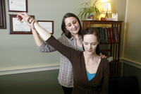 photo of female doctor holding up arm of female patient