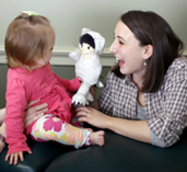 photo of a female entertaining a baby with a puppet